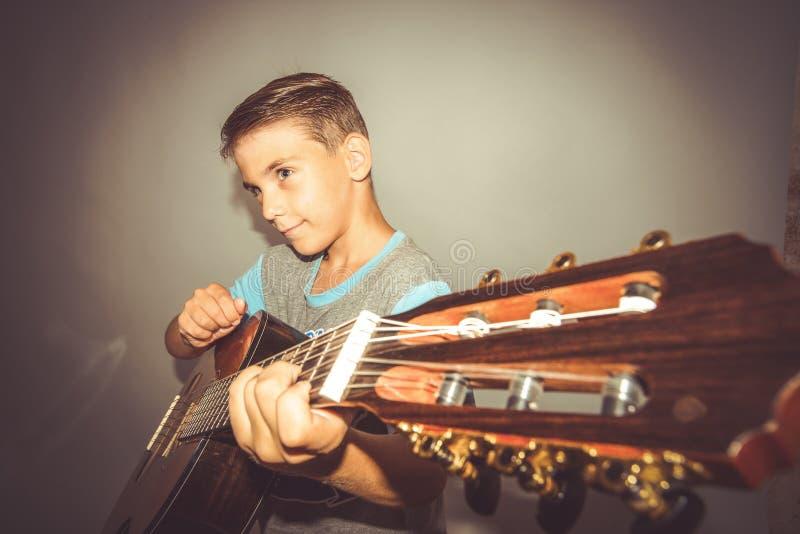 Een jongen speelt de gitaar op een grijze achtergrond in de studio, de brede foto van het hoekclose-up royalty-vrije stock foto