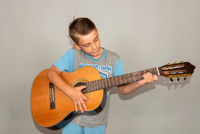 Een jongen speelt de gitaar op een grijze achtergrond in de studio, de brede foto van het hoekclose-up royalty-vrije stock fotografie