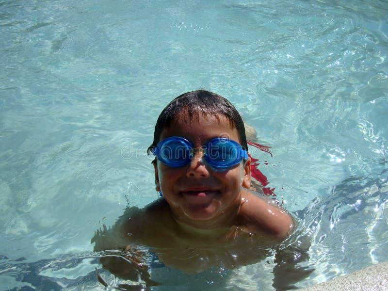 Een jongen speelt in een zwembad met zijn googles stock fotografie
