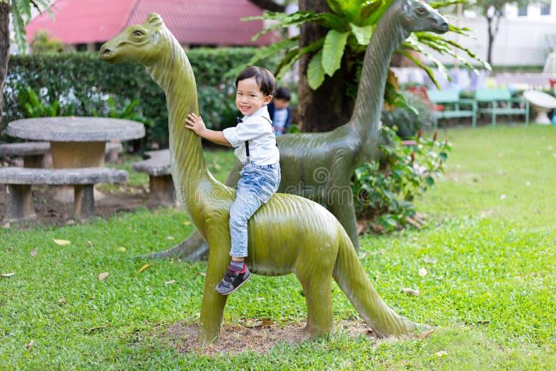 Een jongen speelt en berijdt dinosaurussen met zijn broer bij pl royalty-vrije stock afbeelding