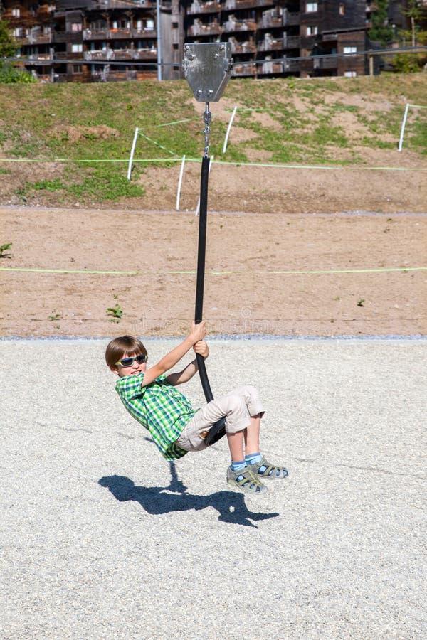 Een jongen speelt met kabelschommeling op speelplaats stock afbeeldingen