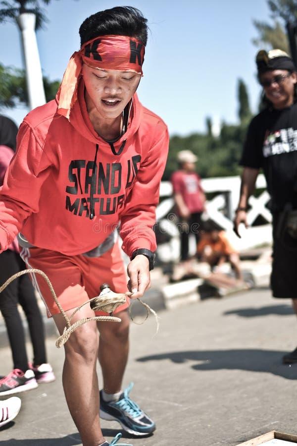 Een jongen speelt tol, traditioneel spel van Indonesië stock fotografie