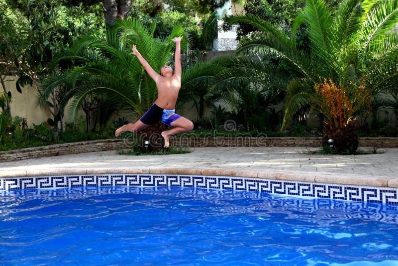 Een jongen springt in een zwembad royalty-vrije stock foto's