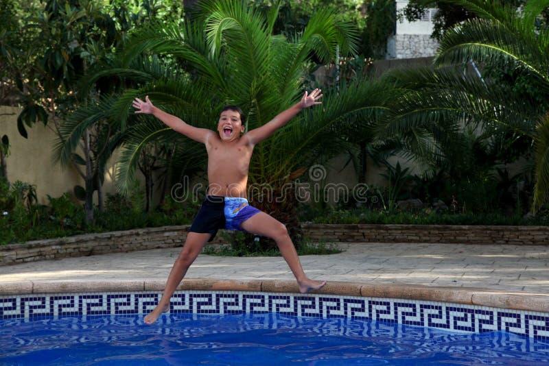 Een jongen springt in een zwembad royalty-vrije stock afbeeldingen
