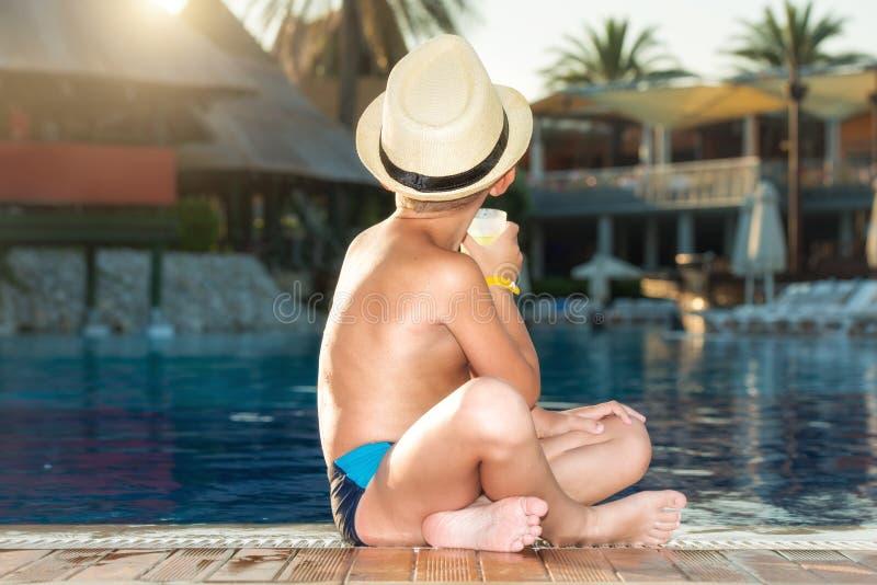 Een jongen in een strohoed met een cocktail in hand zitting op de pool stock foto's