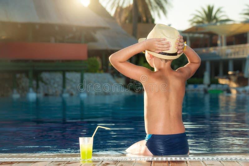 Een jongen in een strohoed met een cocktail in hand zitting op de pool stock foto