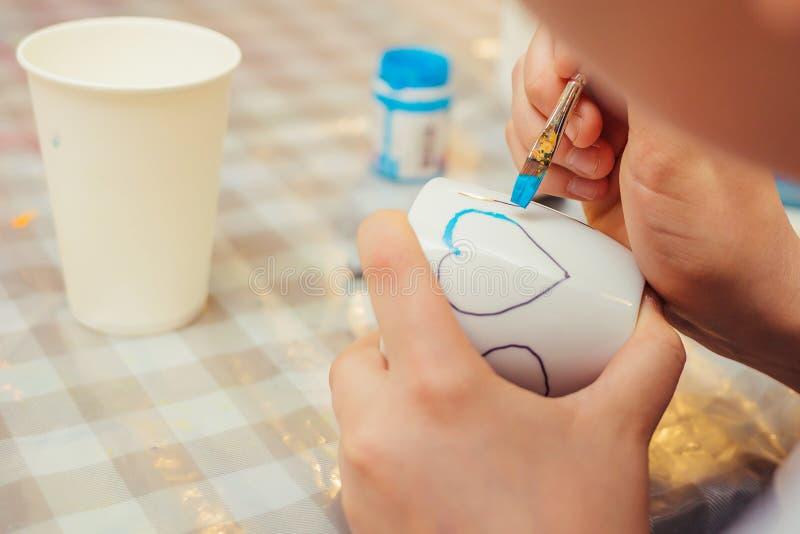 Een jongen trekt een hart op de witte kop met een blauwe verf stock foto