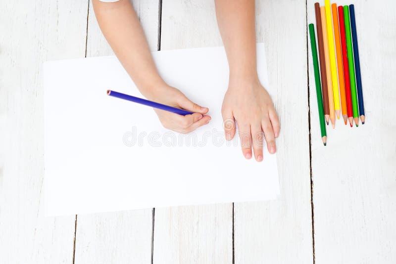 Een jongen trekt met potloden op een wit blad van document Het ontwikkelen van c stock foto's