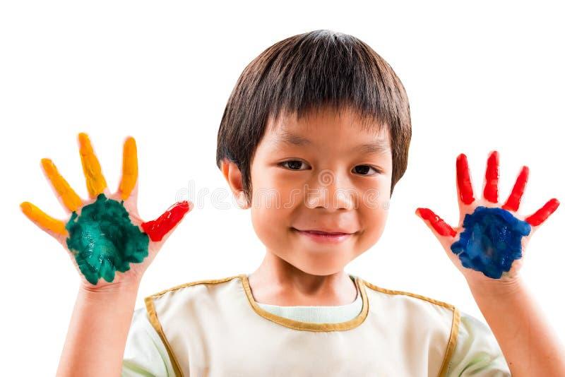 Een jongen van de glimlachkleuterschool heeft pret om zijn hand met kleuren te schilderen stock foto's