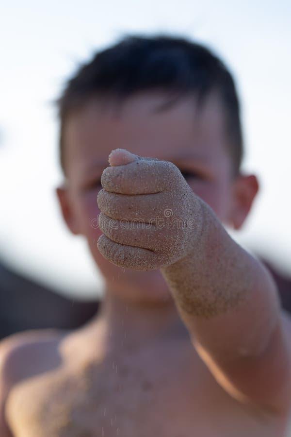 Een jongen van drie jaar die op de speelplaats op het strand spelen De jongen houdt zand in zijn hand Selectieve nadruk royalty-vrije stock afbeeldingen
