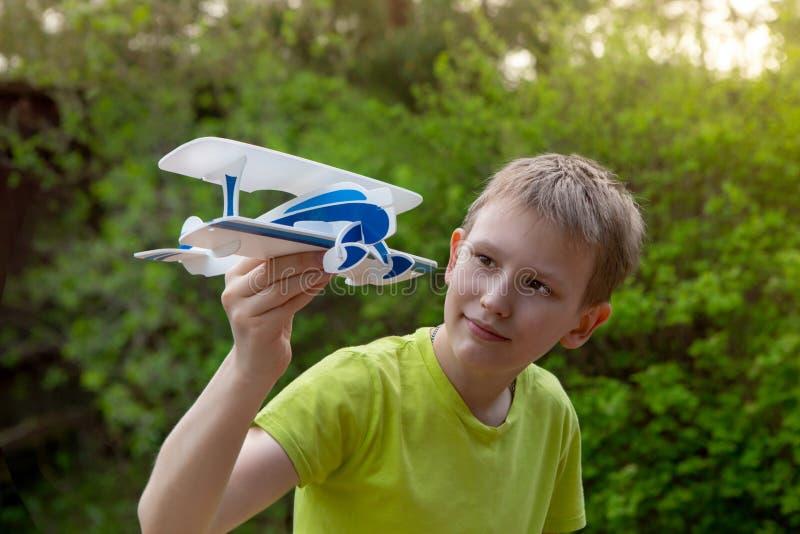 Een jongen van Europese verschijning met een stuk speelgoed vliegtuig op de achtergrond van groen Heldere emoties De stemming van royalty-vrije stock afbeelding