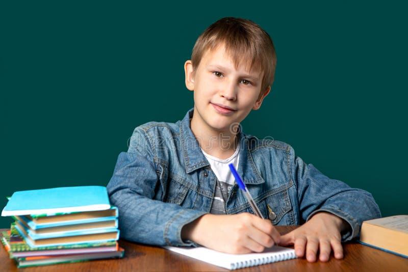 Een jongen van Europese verschijning zit op de achtergrond van de school groene raad Een tiener schrijft in een notitieboekje stock foto