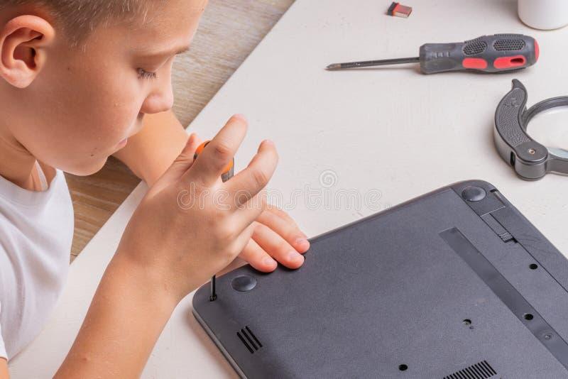 Een jongen van 10 jaar oud sorteert laptop voor het schoonmaken en onderhoud Selectieve nadruk Schroevedraaiers, zuiveringscilind royalty-vrije stock fotografie