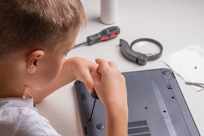 Een jongen van 10 jaar oud sorteert laptop voor het schoonmaken en onderhoud Selectieve nadruk Schroevedraaiers, zuiveringscilind stock afbeelding