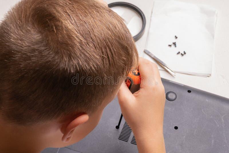Een jongen van 10 jaar oud sorteert laptop voor het schoonmaken en onderhoud Selectieve nadruk Schroevedraaiers, zuiveringscilind royalty-vrije stock afbeeldingen