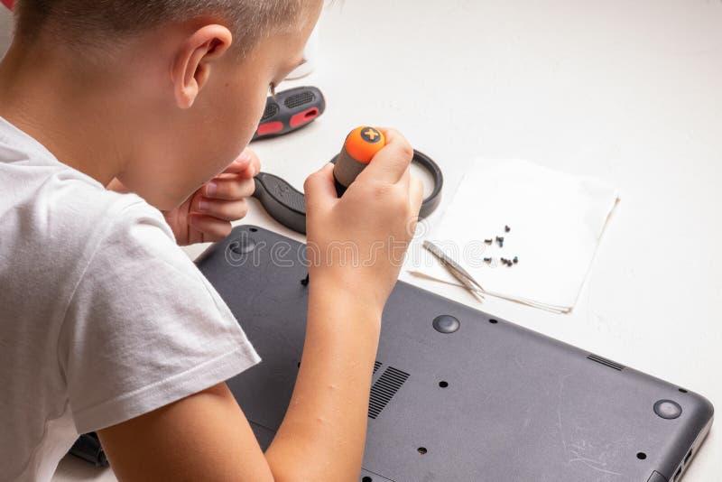 Een jongen van 10 jaar oud sorteert laptop voor het schoonmaken en onderhoud Selectieve nadruk Schroevedraaiers, zuiveringscilind stock fotografie