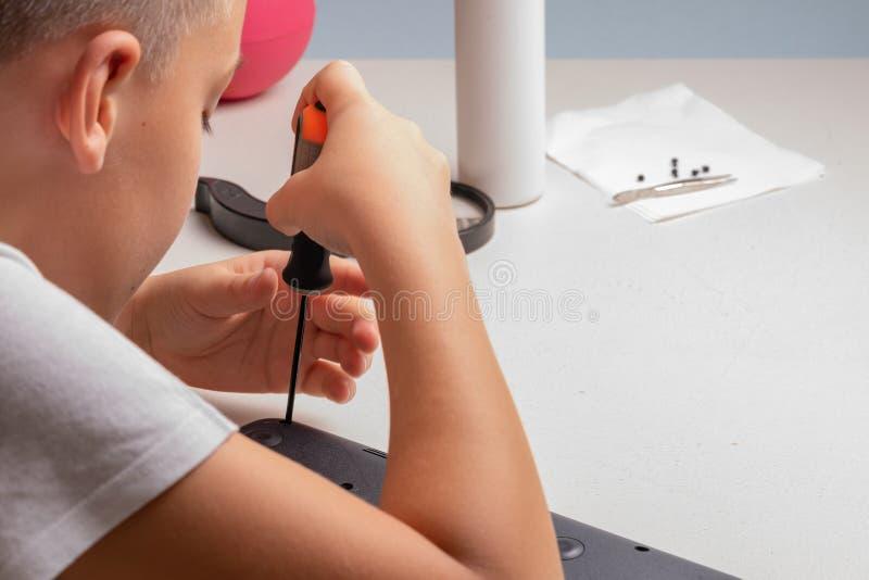 Een jongen van 10 jaar oud sorteert laptop voor het schoonmaken en onderhoud Selectieve nadruk Schroevedraaiers, zuiveringscilind stock afbeeldingen