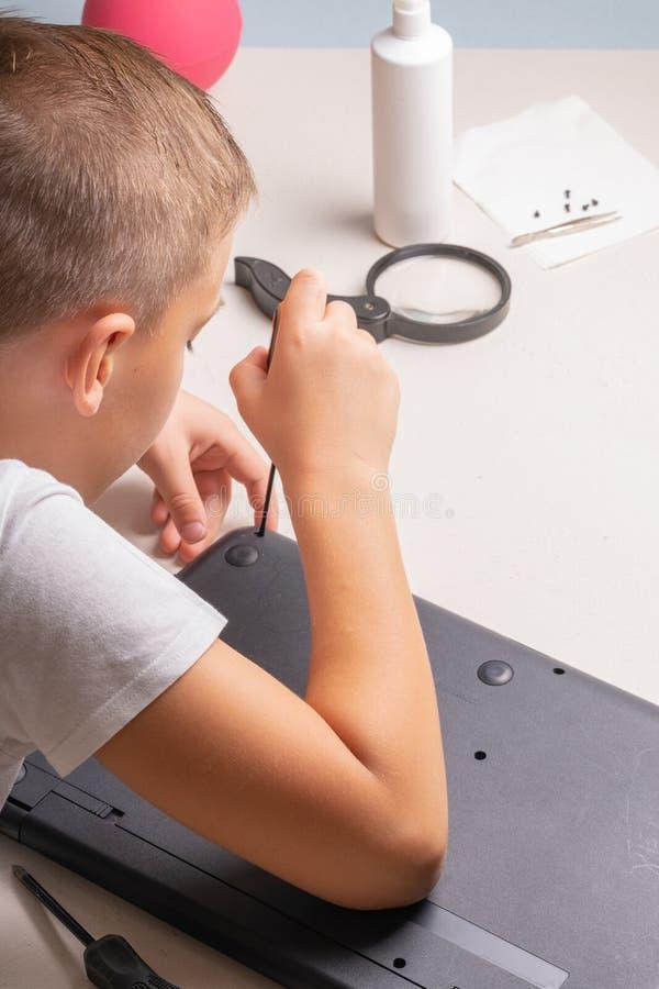 Een jongen van 10 jaar oud sorteert laptop voor het schoonmaken en onderhoud Selectieve nadruk Schroevedraaiers, zuiveringscilind stock foto