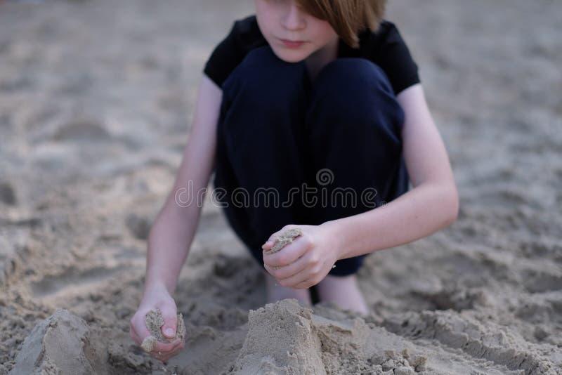 Een jongen van schoolleeftijd het spelen in het natte zand royalty-vrije stock fotografie