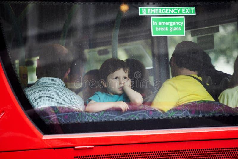 Een jongen van vier bekijkt het achterruit van een bus stock afbeelding