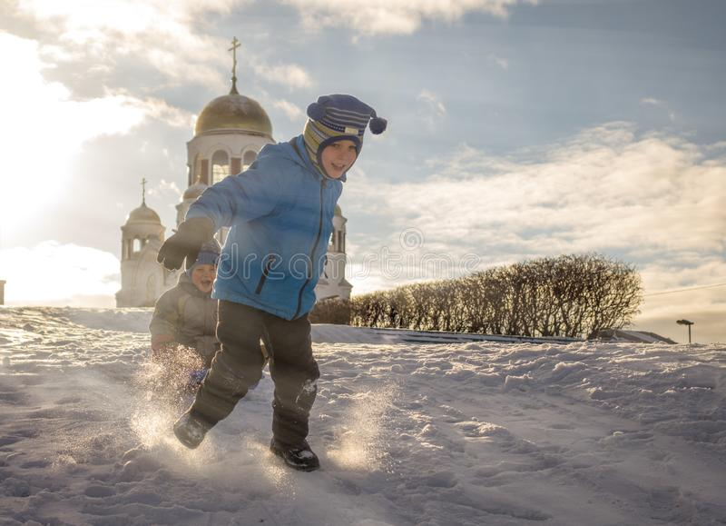 Een jongen vervoert zijn broer op een slee door zuivere sneeuw royalty-vrije stock afbeeldingen