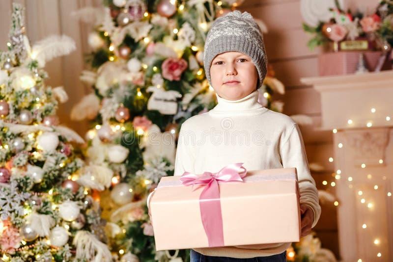 Een jongen zeven jaar die een doos van de Kerstmisgift houden royalty-vrije stock afbeeldingen