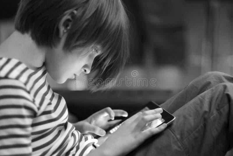 Een jongen zit als voorzitter en speelt een computerspel royalty-vrije stock foto