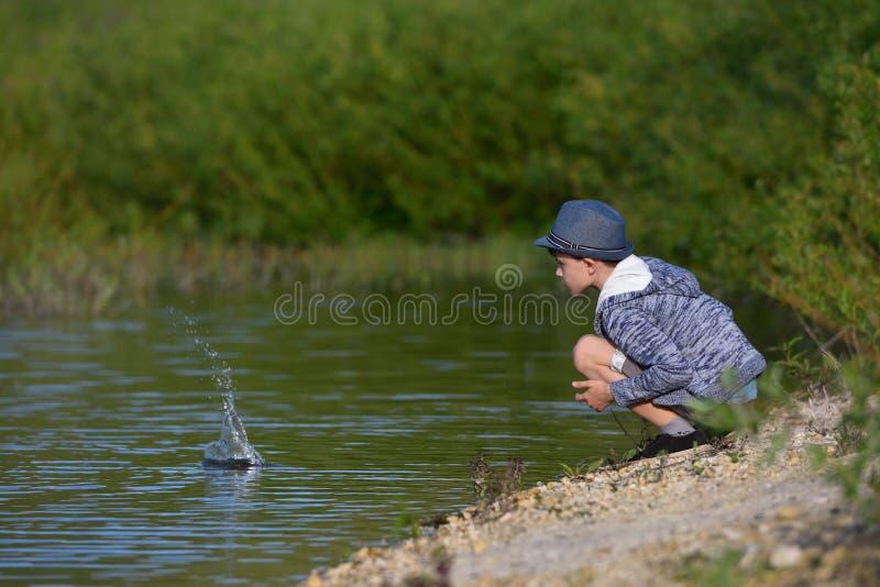 Een jongen zit en werpt stenen in het water royalty-vrije stock afbeelding