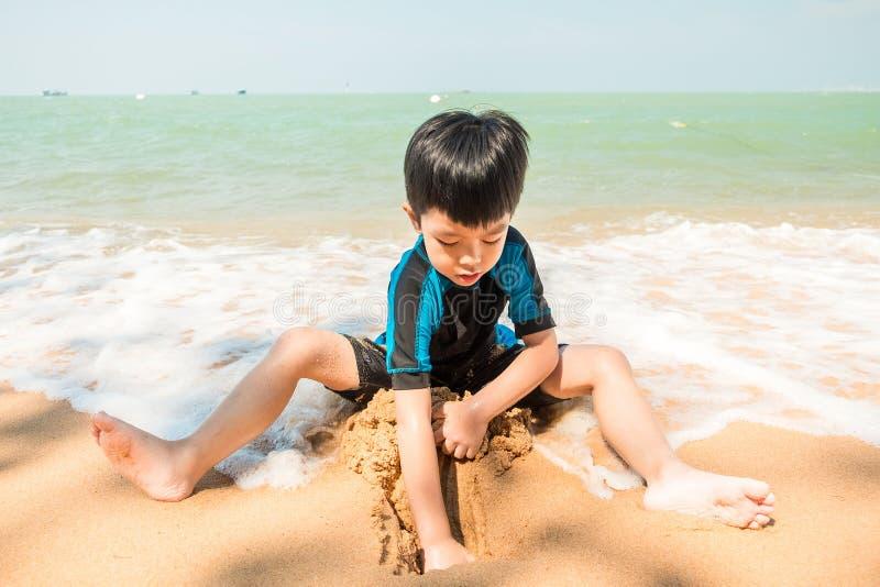 Een jongen in zwemmend kostuum zit op het het strand en het spelen zand royalty-vrije stock afbeelding