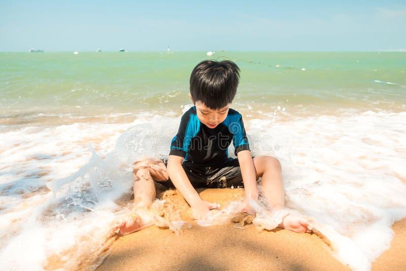 Een jongen in zwemmend kostuum zit op het het strand en het spelen zand stock afbeelding