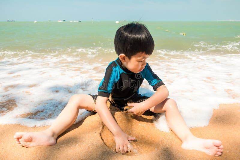 Een jongen in zwemmend kostuum zit op het het strand en het spelen zand stock afbeeldingen