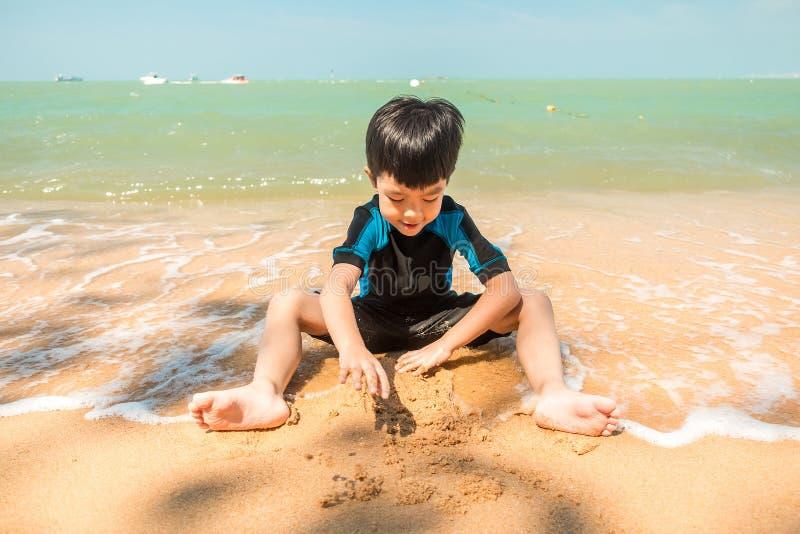 Een jongen in zwemmend kostuum zit op het het strand en het spelen zand stock fotografie