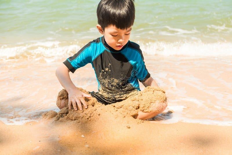 Een jongen in zwemmend kostuum zit op het het strand en het spelen zand royalty-vrije stock foto