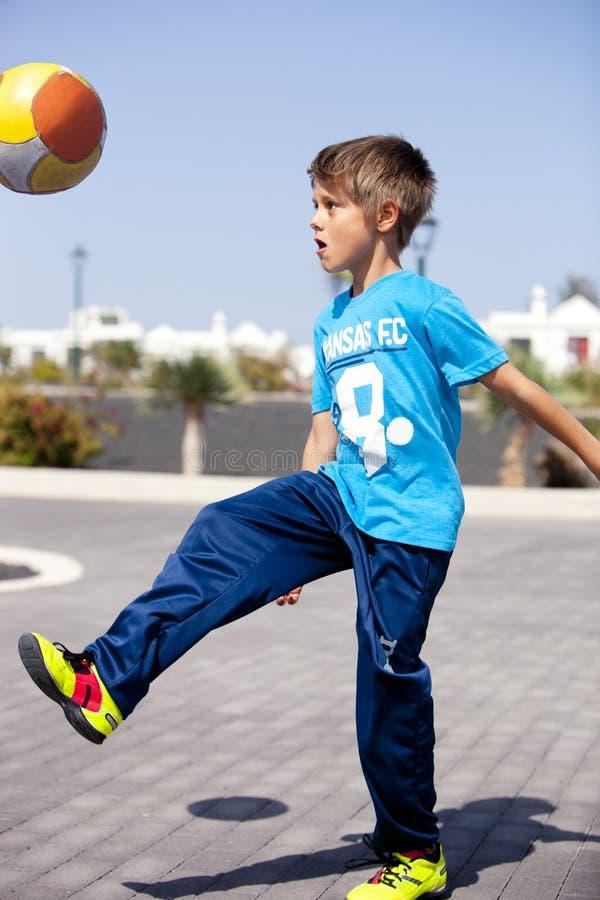 Een jongens speelvoetbal stock afbeeldingen