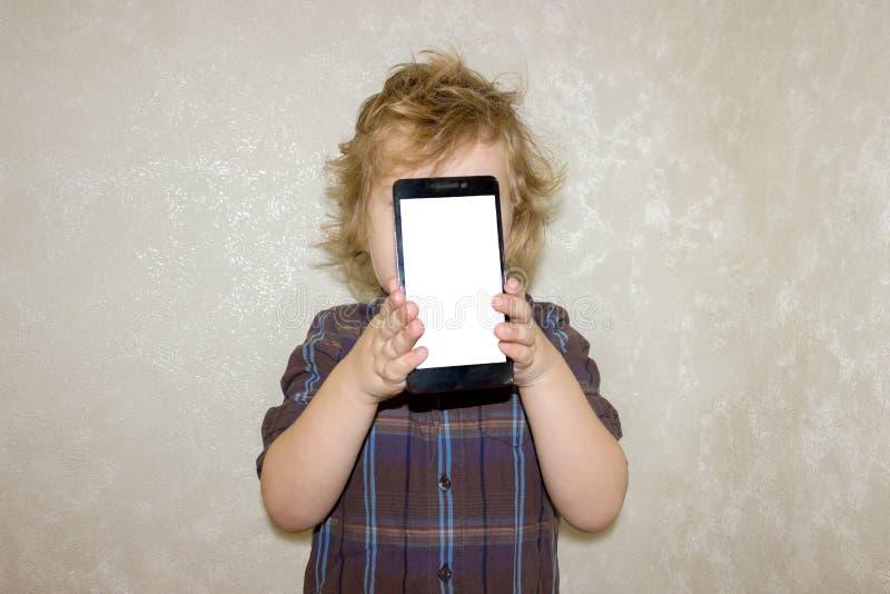 Een jongensjong geitje onderzoekt de camera van een smartphone, toont het scherm met zijn digitale foto stock fotografie