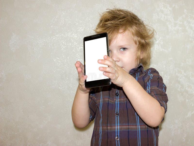 Een jongensjong geitje onderzoekt de camera van een smartphone, toont het scherm met zijn digitale foto stock afbeelding