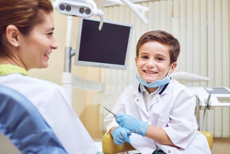 Een jongensjong geitje is een tandarts met een patiënt bij een tandkliniek stock fotografie