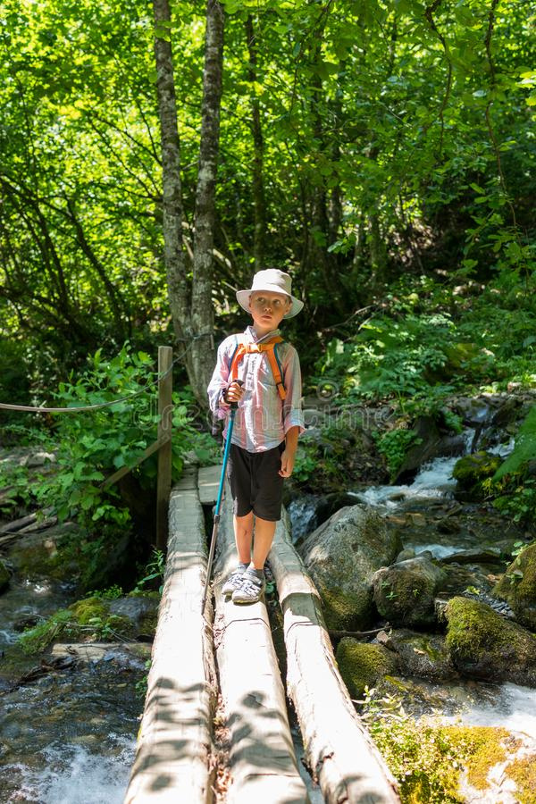 Een jongensreiziger met een trekkingspolen bevindt zich op een rachitische brug over een snelle stroom stock afbeelding