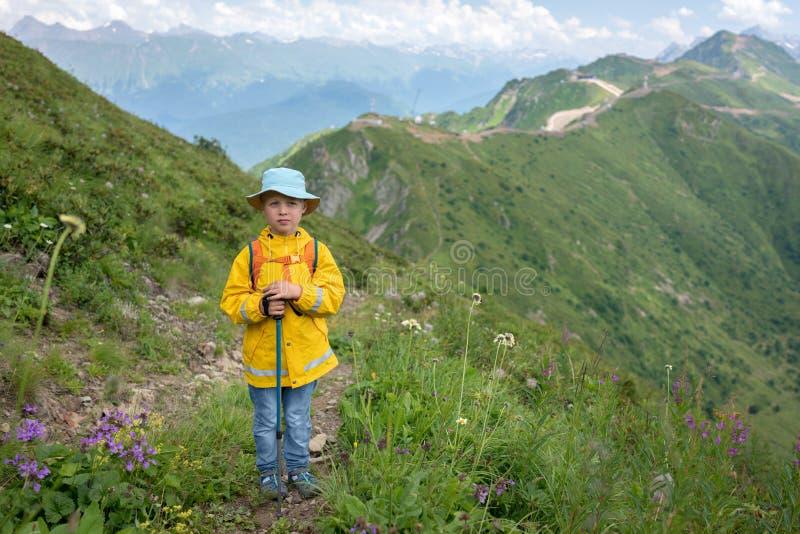 Een jongensreiziger met trekkingspolen in een gele regenjas en Panama bevindt zich op de weg tot de bovenkant van de bergketen stock fotografie