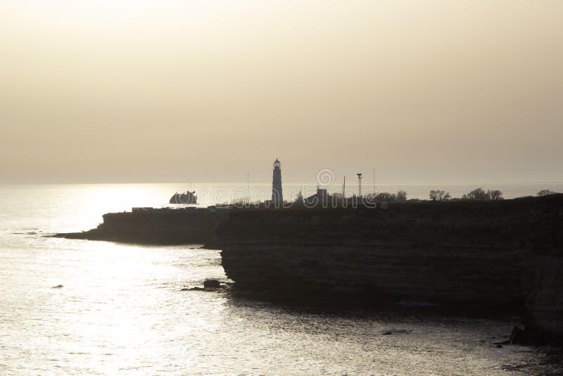 Een kaap met een vuurtoren bij zonsondergang Tarkhankut, de Krim stock fotografie