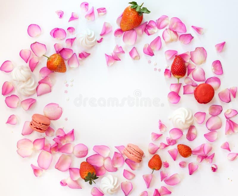 Een kader met roze roze bloemblaadjes, suikersterren, aardbeien, mereng royalty-vrije stock foto