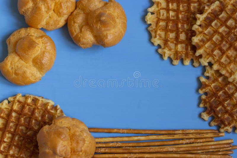 Een kader van snoepjes, blauwe houten die achtergrond in profiteroles, Weens wafels en suikerstro wordt ontworpen De achtergrond  stock foto's