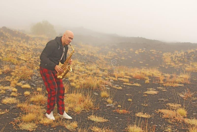 Een kale mensenspelen op een gouden altsaxofoon in de aard, tegen royalty-vrije stock foto's