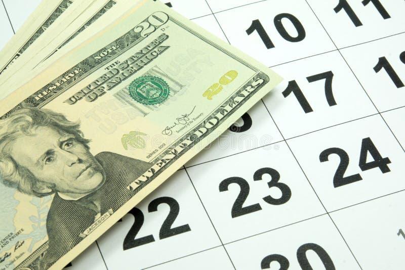 Een kalender en een dollarsgeld stock foto