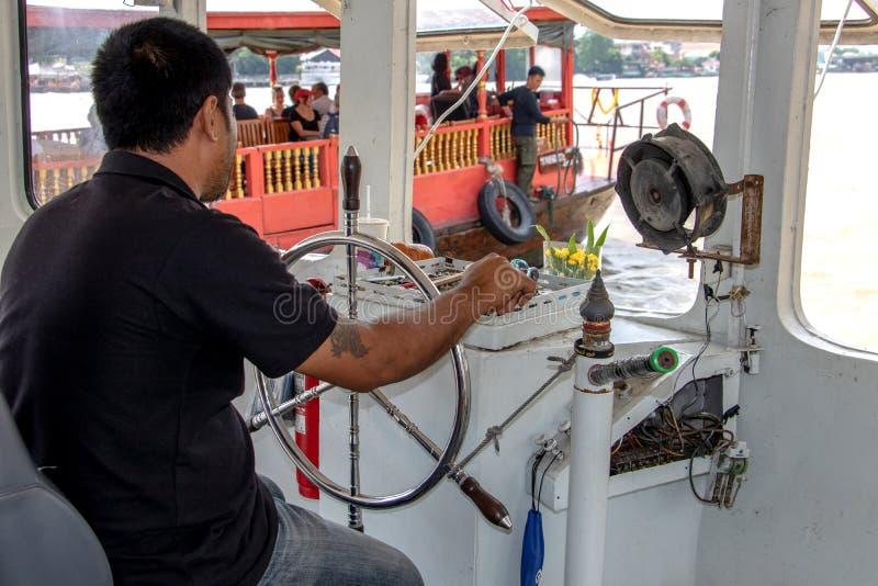 Een kapitein drijft een boot stock afbeeldingen