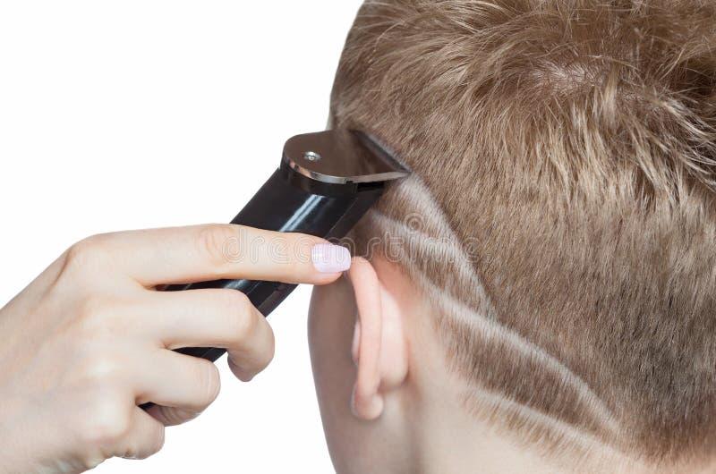 Een kapper doet een kapsel voor een jonge mens in een herenkapper stock foto's
