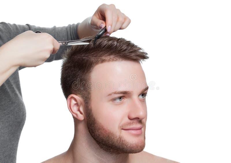 Een kapper doet een kapsel voor een jonge mens in een herenkapper stock fotografie