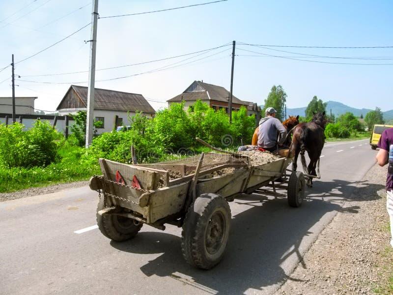 Een kar door twee paarden wordt getrokken berijdt op een bedekte landelijke weg in Khust die royalty-vrije stock afbeeldingen