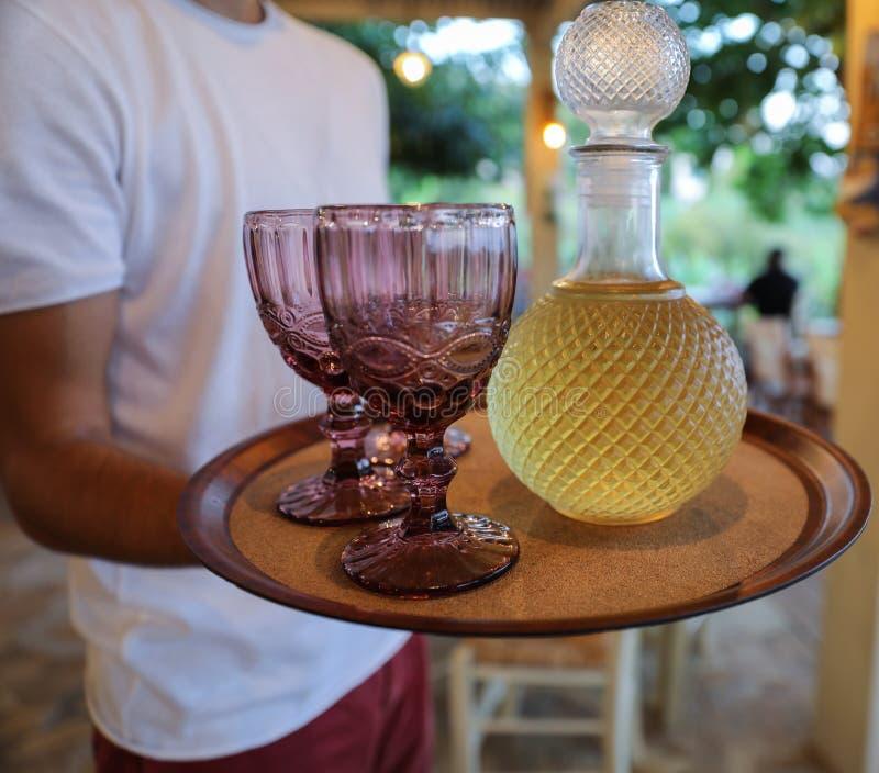 Een karaf met witte wijn en twee glazen op een dienblad bij de kelner in een restaurant op het Kefalonia-eiland, Ionische overzee stock afbeeldingen