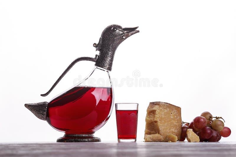Een karaf rode wijn, een glas wijn, dure kazen, kaas met vorm, zwarte kaas en druiven stock foto's